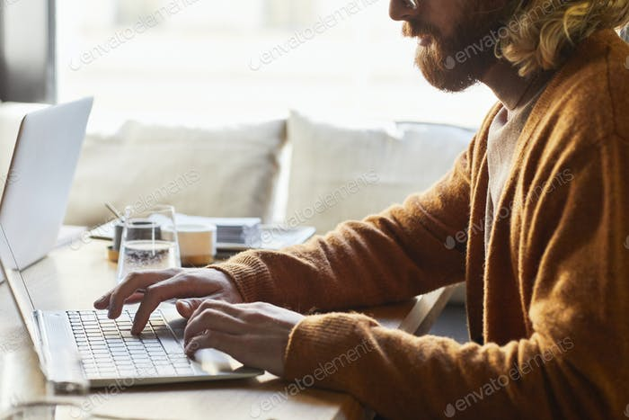 Freelancer Using Computer at Cafe Table
