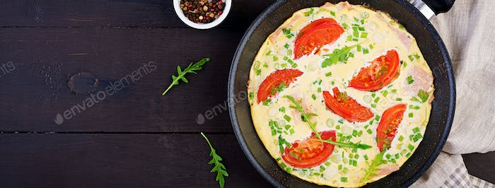 Omelette with tomatoes, ham and green onion on dark table.  Frit