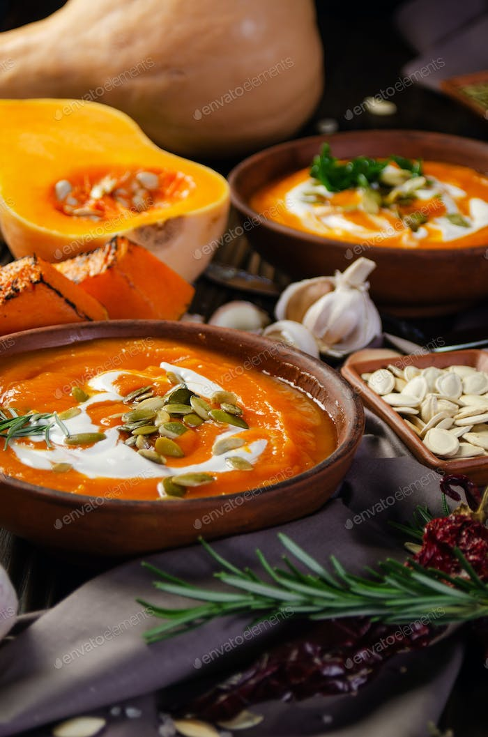 Homemade rustic pumpkin soup with seeds in clay dish