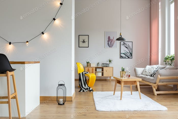 Gallery of posters on the wall of stylish living room with woode