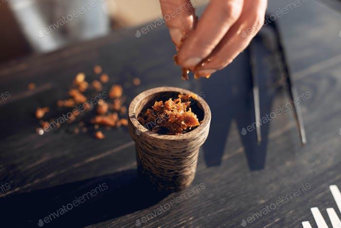Beschnittene Ansicht der Zubereitung von Tabak für Shisha auf Tisch außerhalb