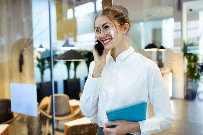 Stylish young businesswoman talking with her mobile phone while