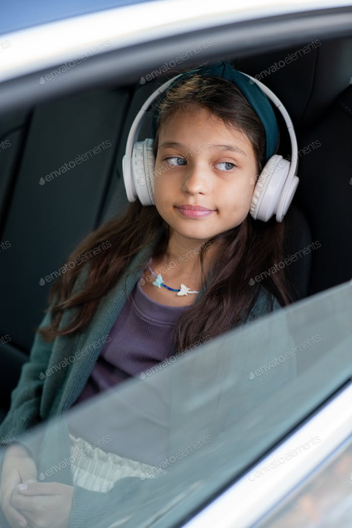 Cute little girl listening to music in headphones while sitting in car