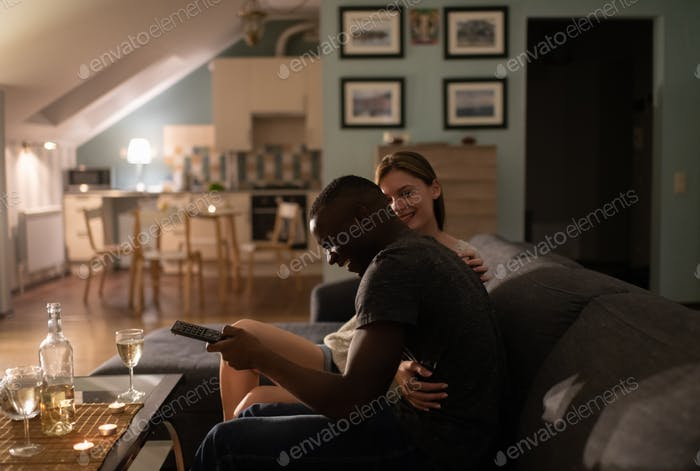 Excited diverse couple watching TV