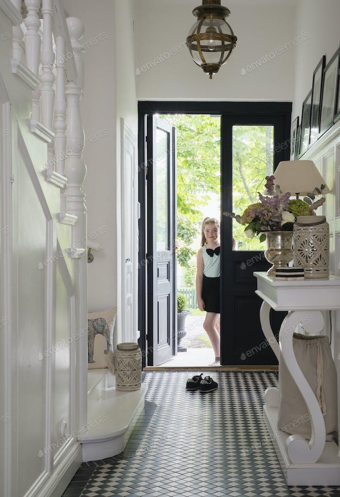 Girl (10-11) standing in front door