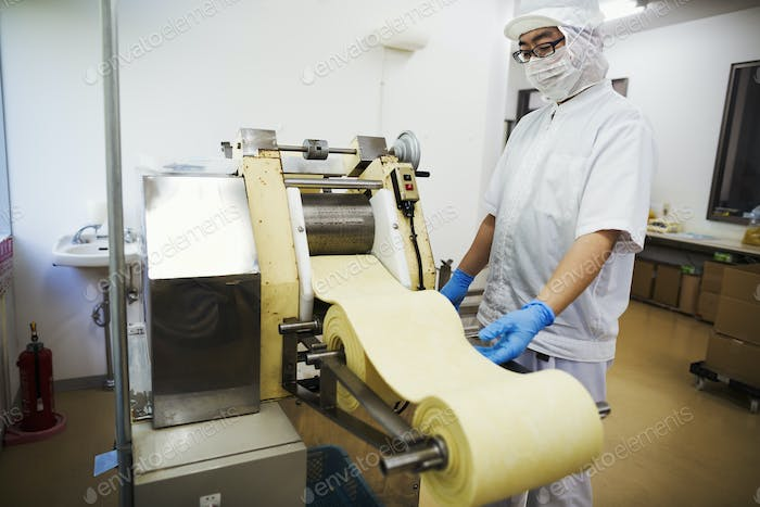 Worker in a factory producing Soba noodles