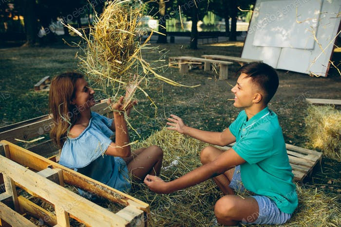 guy and girl throwing hay