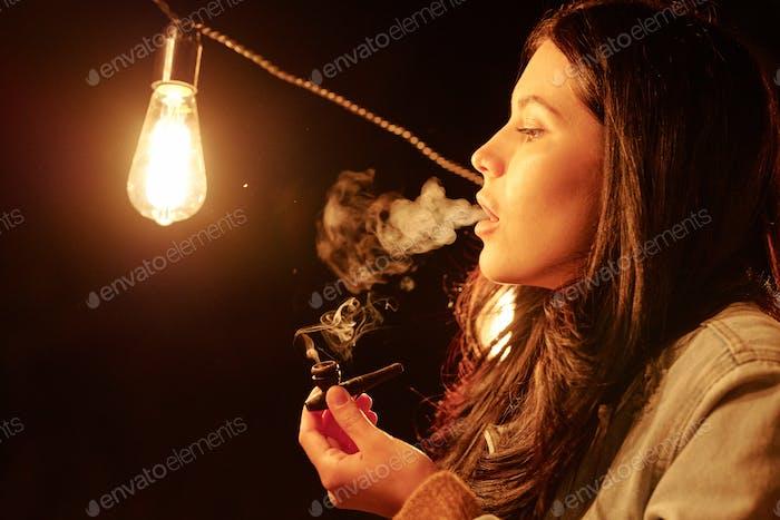 Junge Frau mit dunklen langen Haaren halten Holz Tabakpfeife beim Rauchen