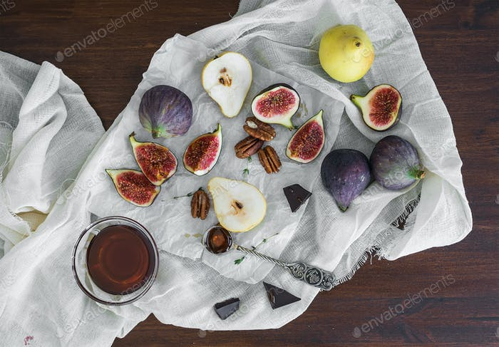 Fresh figs, chocolate, pears and pekan nuts with honey on a wood
