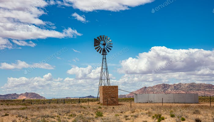 Windmill in a field, sunny spring day, blue sky with clouds background.