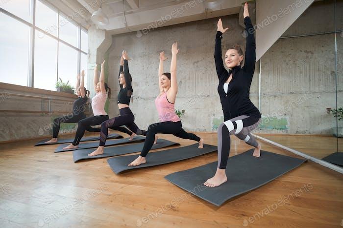 Gruppe von Fitnessfrauen Stretching auf Matten