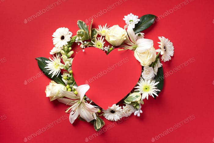 Creative layout with white flowers, paper heart over red background. Top view, flat lay. Spring and