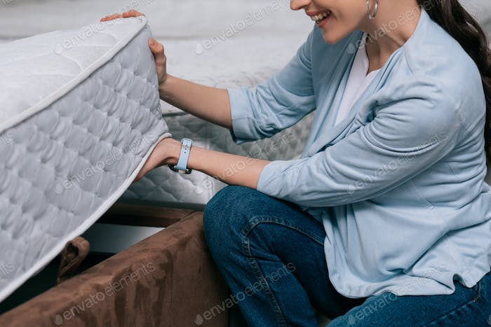 cropped shot of smiling woman choosing orthopedic mattress in furniture store