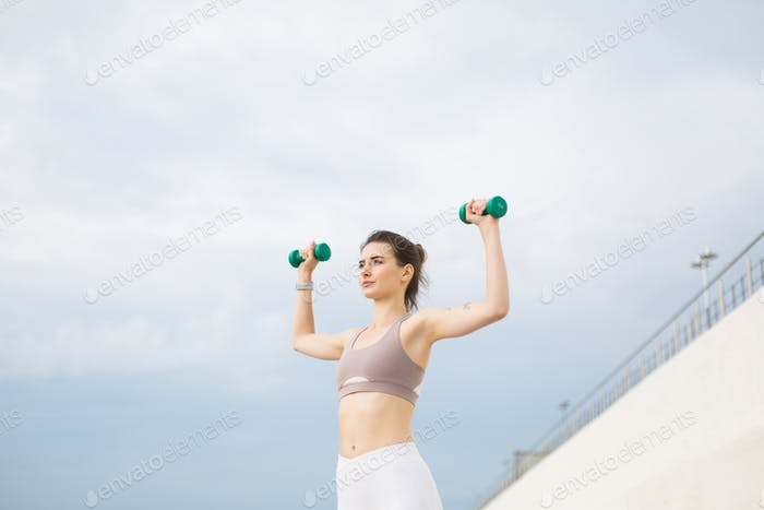 Young woman in sporty top doing exercises with dumbbells in hand