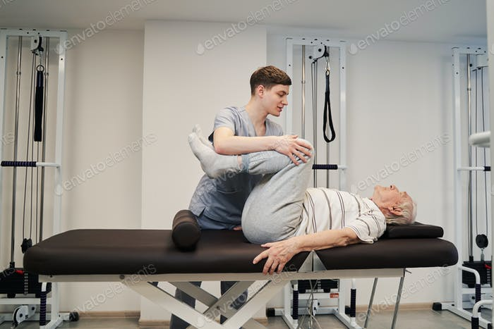 Physician helping old person with therapeutic exercise for legs
