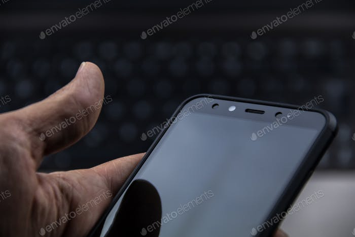 hand of senior person using a modern mobile in a workspace