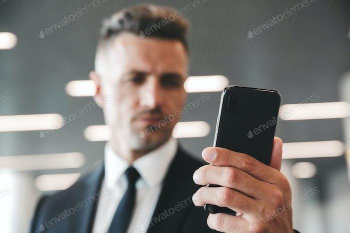 Serious mature businessman looking at mobile phone