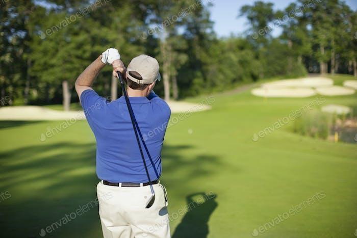 Golfer Hitting onto Defocused Green