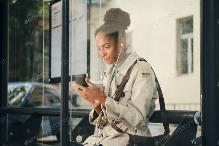 Beautiful African American girl in stylish trench coat happily using cellphone at bus stop