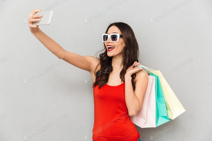 Cheerful brunette woman in casual clothes and sunglasses making selfie