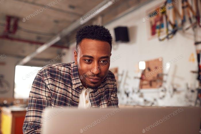 Männliche Zimmermann In Werkstatt tun Konten auf Laptop