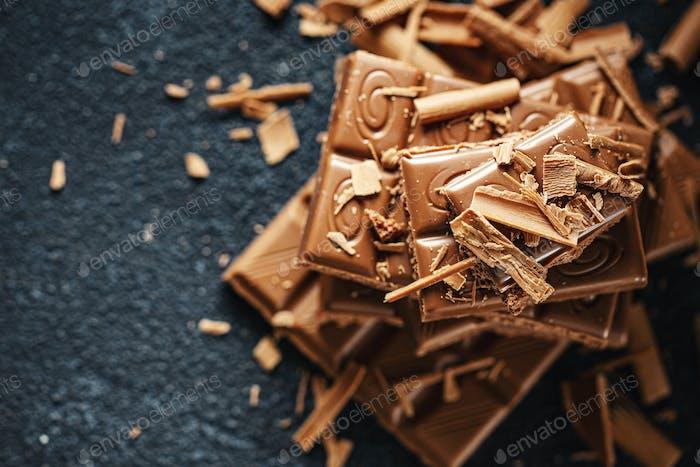 Broken chocolate bars on dark background