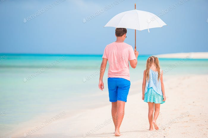 Young father and his little daughter walking under umbrella on white sand beach
