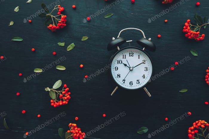 Alarm clock on dark background, flat lay