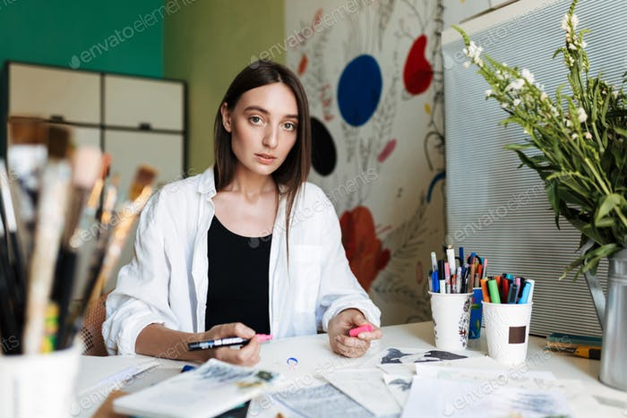 Young pensive girl sitting at the desk dreamily looking in camer