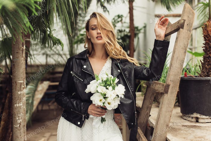 Young pretty woman in black leather jacket and white dress with
