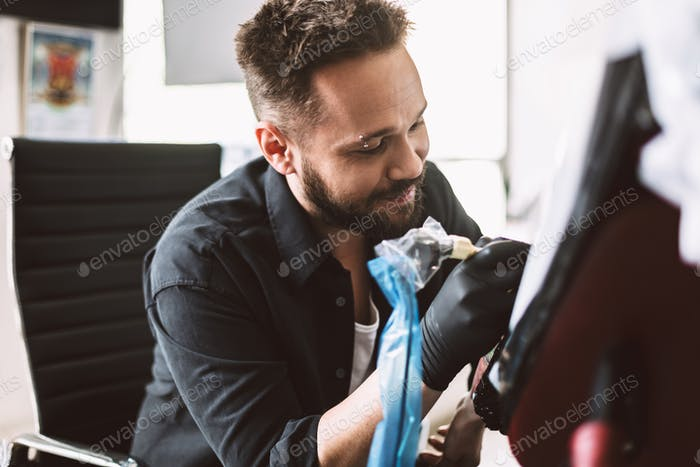 Smiling professional tattooer doing tattoo on client hand by tat