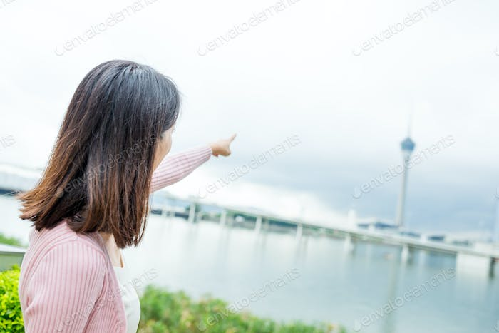 Woman finger pointing to the landmark in Macao
