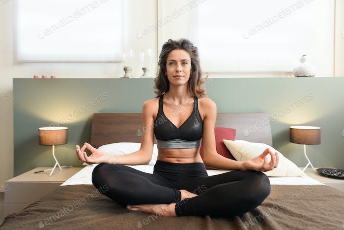 Fitte gesunde Frau meditiert im Schlafzimmer