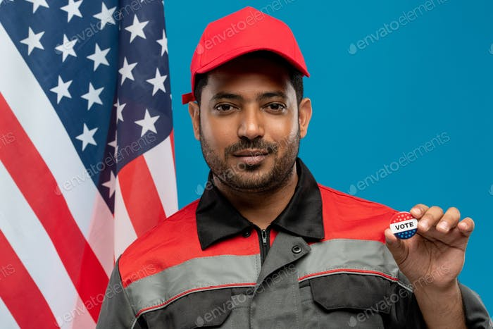 Young serious repairman of Hispanic ethnicity showing you vote insignia