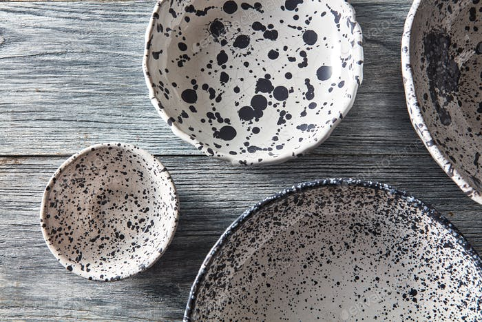 Clay handcraft empty bowls, plates, covered with glazed , place under text on a gray wooden