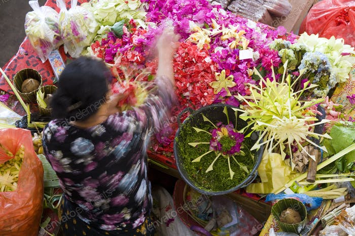 High angle view of woman at Asian flower market, flower arrangements and heaps of colourful