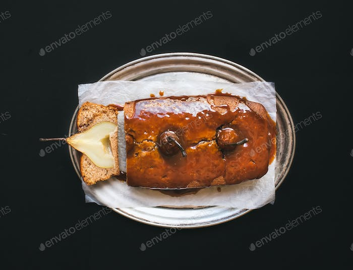 picy pear cake with caramel topping on a silver dish over a dark