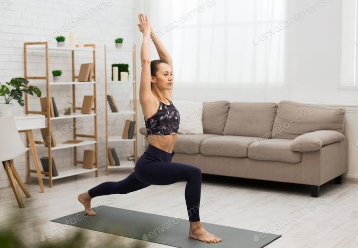 Athletic woman doing yoga, stretching exercise at home