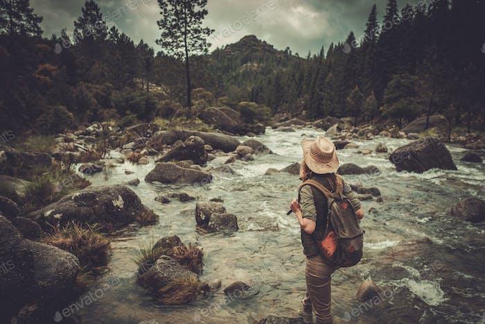 Thumbnail for Beautiful woman hiker enjoying amazing landscapes near wild mountain river.