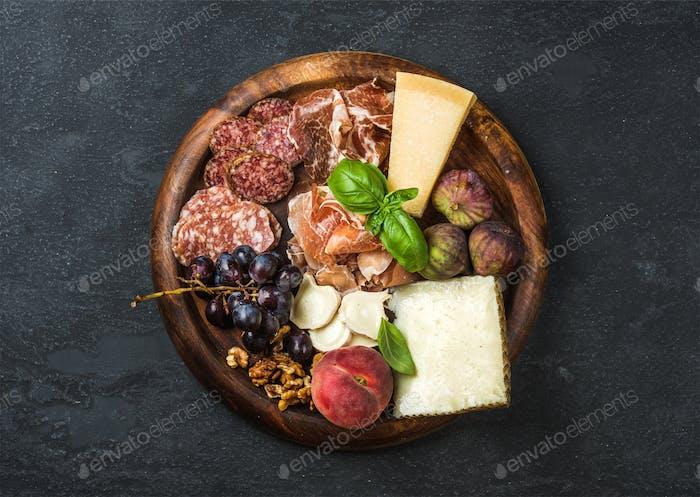 Italian antipasti snacks variety for wine on wooden tray