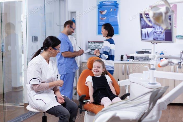 Dentist in dental office making little girl laugh