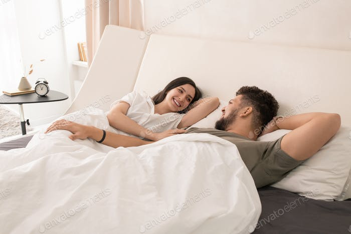Young amorous couple lying in bed