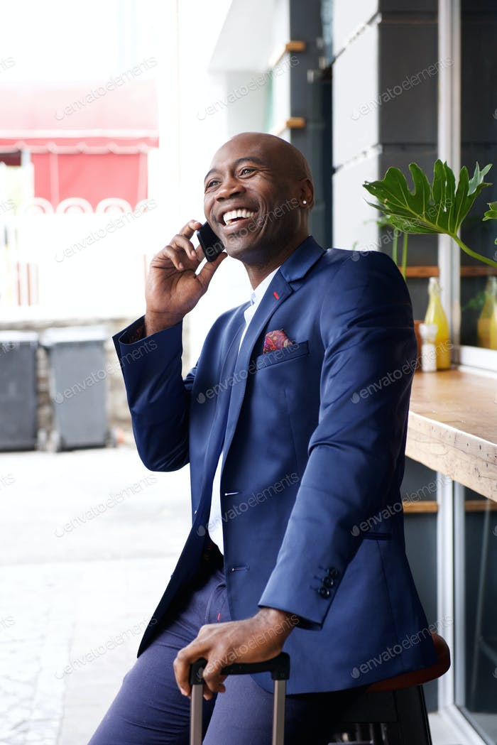 African businessman with a bag talking on mobile phone