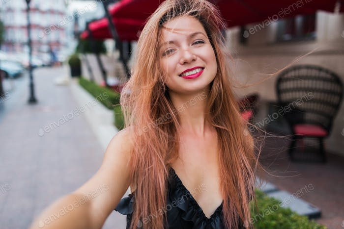 Playful cute red hears woman smiling  and making self portrait