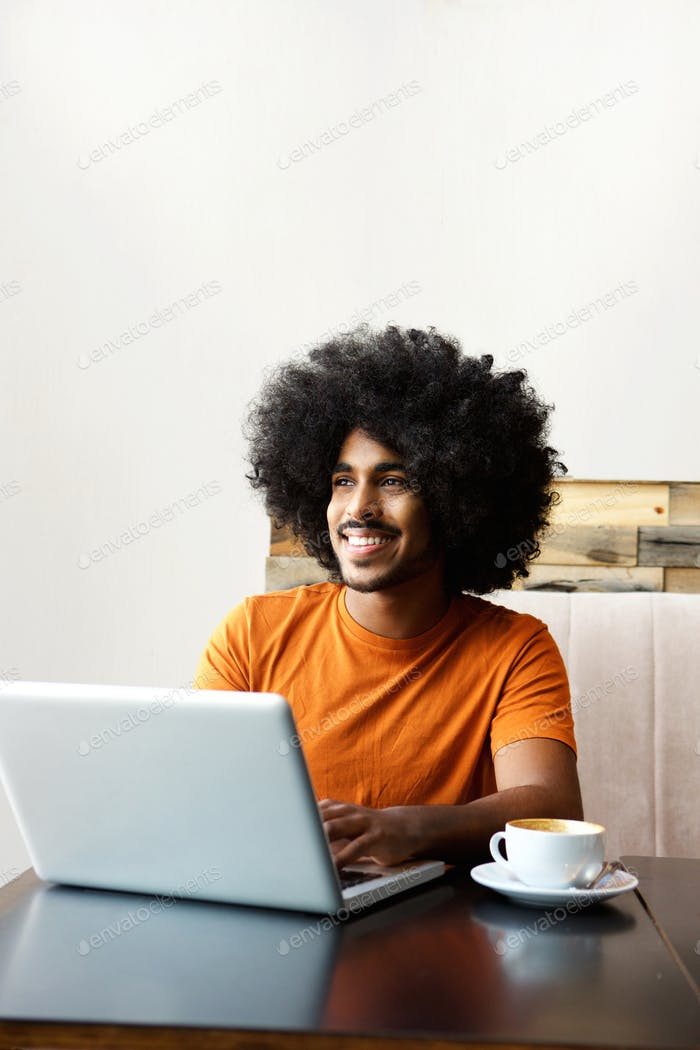 Smiling man sitting at table with laptop