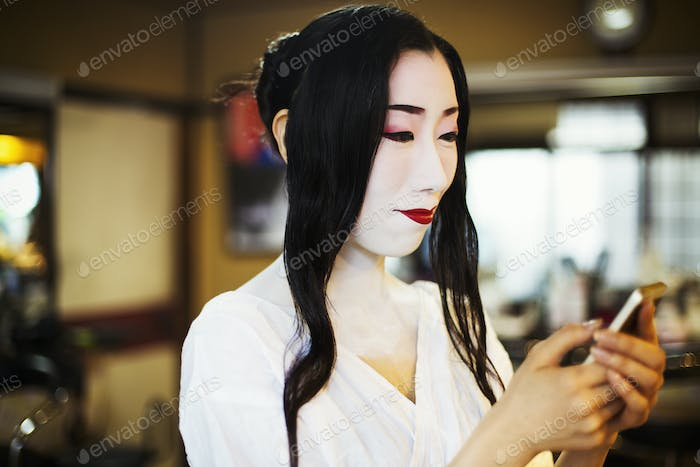 Geisha with long black hair and traditional white face make up  using a smart phone.