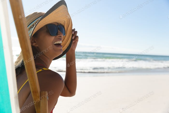 Mixed race happy woman on beach holiday sitting in deckchair