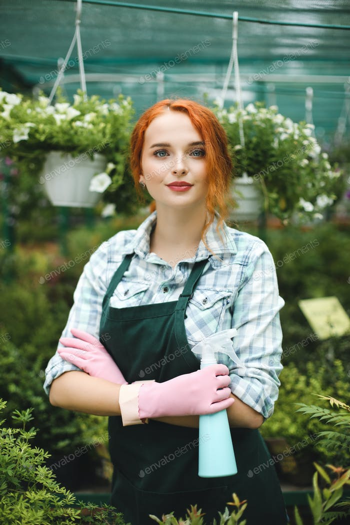 Pretty lady in apron and pink gloves standing with spray bottle in hand and dreamily