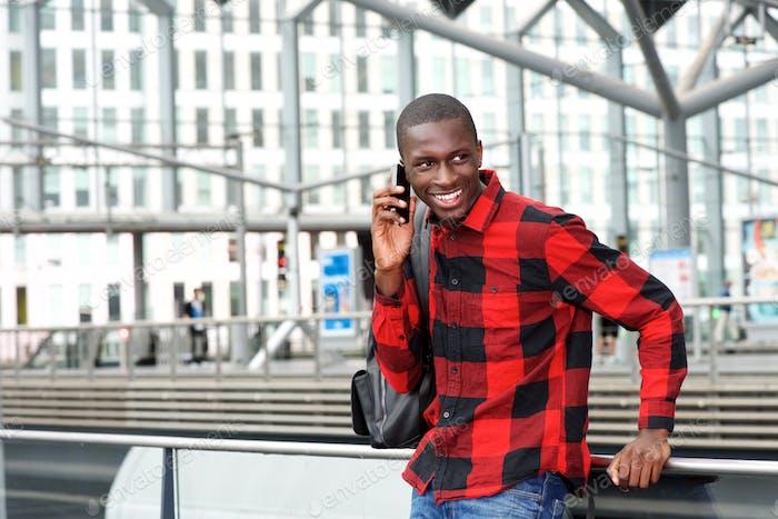 Glückliche junge Kerl am Bahnhof mit Handy