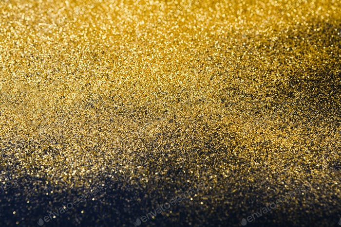 Golden glitter sand texture on black, abstract background.